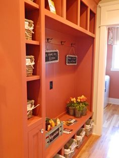 this is a  Mudroom in Orange color with natural lighting and use of natural , real plants. have a good storage space for clothes and shoes. it looks refreshing and bright. i gives a happy feeling.