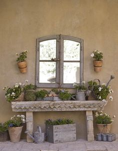In a new Phoenix, Arizona home, designer Dana Lyon achieved a French country style by using antiques and natural materials. The stone potting table in this front courtyard is from On the Veranda.   - HouseBeautiful.com