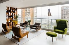 In an apartment overlooking São Paulo's Ibirapuera Park—completed in 1954 to commemorate the city's 400th anniversary—the furniture is as distinctive as the view. Architect Flavio Castro of FCstudio worked closely with the residents to update and outfit the home, which is appointed with a mix of contemporary and Brazilian modern classics. A pair of Sérgio Rodrigues's Paraty armchairs (in foreground)—designed for Brasilia's Itamaraty Palace in 1963—face a duo of Jader Almeida's Isa armchairs…