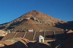 """View of Rich Hill (Cerro Rico) and National Mint. Potosí lies at the foot of the Cerro de Potosí[3]—sometimes referred to as the Cerro Rico (""""rich mountain"""")—a mountain popularly conceived of as being """"made of"""" silver ore, dominates the city. The Cerro Rico is the reason for Potosí's historical importance, since it was the major supply of silver for Spain during the period of the New World Spanish Empire."""