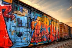 """""""GZRAM!"""" ©Janelle DeRuosi 2012.  Escalon Packers, a local tomato sauce plant, always has railcars waiting to be filled outside.  I saw this uniquely graffitied car one day and grabbed my camera knowing I'd never see it again.  At sunset I was suddenly dazzled by a sky full of God's rays as the sun went behind a low cloud.  I especially like this angle with the graffiti art filling the frame on the far left before flowing out into the cars, giving a feeling of art coming to life."""