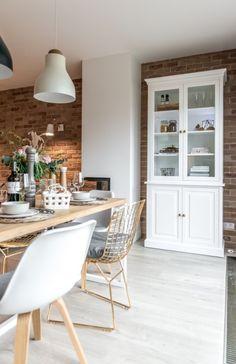 Całą ścianę w jadalni oraz salonie wyłożono czerwonymi cegłami. Na ich tle pięknie prezentują się jasne meble,...