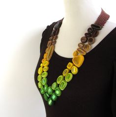 """Laura Luepke, Fade Out Necklace, """"51 cabochons surrounded by 25 different sizes, hues, and finishes of seed beads to create subtle color transitions from brown to green resulting in an ombre effect"""""""