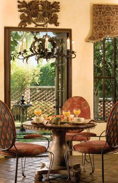 A wooden crest hangs above the doorway between the courtyard and breakfast room, where a Lee Jofa print dresses iron chairs from Arte De Mexico.