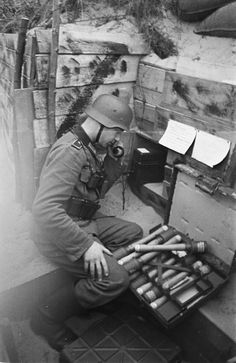"German soldier in a trench, located in the dunes on North Sea coast, listens on a field phone. Next to him, ""Stick Hand Grenade 24"" (Stielhandgranate 24). Netherlands, 1942."