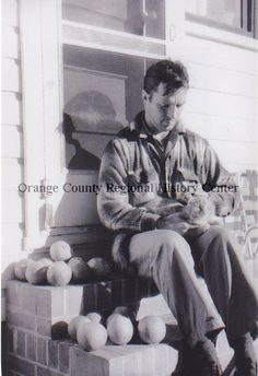 """Jack Kerouac, lived in Orlando and wrote one of his most important works, """"The Dharma Bums,"""" in a small tin-roofed house near downtown.  Jack Kerouac sitting outside his house with his cat. 1958. Orange County Regional History Center."""