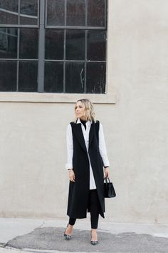 Create an alternative smart casual look by pairing a sleeveless long jacket with a simple white blouse and black cigarette trousers. Via Jacey Duprie. Sleeveless Blazer Outfit, Sleeveless Jacket, Blazer Outfits, Fall Outfits, Work Outfits, Black Cigarette Trousers, Cute White Dress, Outfit Trends, Outfit Ideas