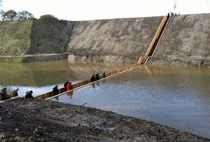 """No, your eyes are not deceiving you - the waters have indeed parted! This incredible """"sunken"""" bridge located in the Netherlands is giving visitors a unique way to access a beautiful 17th Century Dutch fort. Designed by RO & AD Architects, the Moses Bridge literally parts the waters that surround the fort, allowing pedestrians to pass through."""