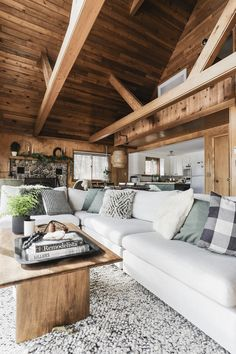 A white modular sofa gives a woodsy Wisconsin cabin a modern edge, creating a super comfy sunken living room vibe with low deep seats and feather cushions.