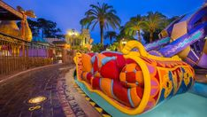 A section of The Magic Carpets of Aladdin attraction next to a huge camel statue at night
