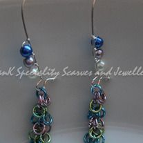 Blue, lilac and cream 4mm glass pearl beads are woven onto stainless steel kidney hooks with a chainmaille dangle of pink, green and blue.