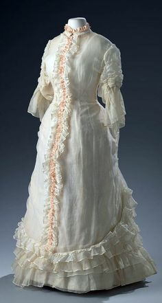 White summer dress of thin transparent cotton with pink silk trim, ca. 1870-75. Fitted princesses-style cut, high collar with half-long, shirred sleeves, pink ruffle on front closure (with hooks & eyes). Trimmed with Valenciennes lace. Amsterdam Museum