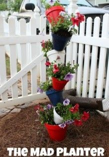 """I always wanted to make one of these just w/ plain pots- strawberry tower maybe? a succulent tower would be cool too... or maybe mosquito repelling plants...  (1) 8"""" clay pot  (6) 6"""" clay pots  10 ft rebar  Potting soil  Flowers"""