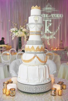 Kandi Burruss – star of The Real Housewives of Atlanta – and her husband's wedding cake was a towering confection fit for royalty. Tiers featured various shapes and were adorned with crystals, golden draping, and a crown topper. Photography: Robin Gaucher Photography. Read More: https://www.insideweddings.com/weddings/kandi-burruss-and-todd-tucker/560/