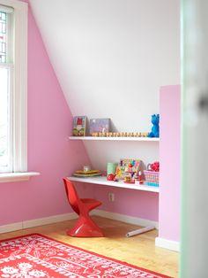 In deze vrolijke kinderkamer is een simpele knutselhoek gemaakt door een paar planken tegen de muur te bevestigen en er een stoeltje voor te zetten.