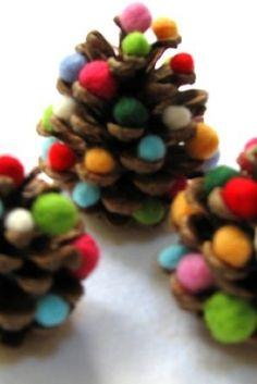 Se trata de un mini arbolito de navidad, realizado con piñas secas y bolitas de colores realizadas con lana. Es fácil, os hacéis con un poquito de lana de colores, no tiene por qué ser de un color mate, podéis comprarla brillante en tonos dorados o plateados, hacéis unas bolitas y las encajáis a la perfección en cada uno de sus palitos, donde guardaron en un pasado sus piñas.