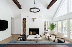 Wohnzimmer im Landhausstil einrichten, Hirschkopf an der Wand, Bücher und Hölzerturm, verspielter Kronleuchter, Ledermöbel