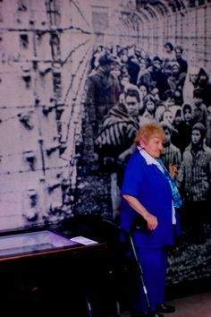 Survivor in front of her picture in the camp of Auschwitz in 1945