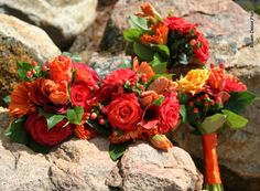 Bright and cheery bridesmaid's bouquets. Red roses, orange roses, orange tulips, red gerbera daisies, red hypericum berries and lemon leaf.