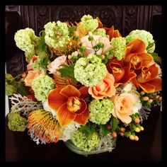 Viburnum, pin cushion proteas and brown cymbidium orchids featured in this floral arrangement!