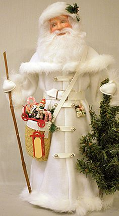Frost is entirely hand crafted by Canadian Santa Artist Shirley Ivison. Santa wears a long, white, plush coat and cap with white fur trim. He stands by an evergreen tree and carries a woven basket full of toys and goodies held by a strap across his chest.