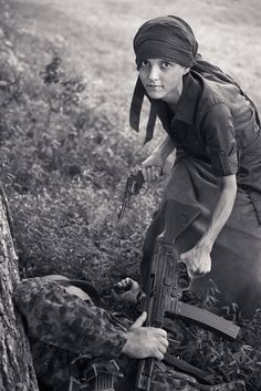 """OOPS, MODERN RE-ENACTORS -- """"A partisan takes a trophy STG44 rifle from a dead SS Panzergranadier.""""  At link, next photo is a color shot of same woman in different pose."""