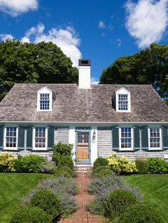 this is it...my little cape cod dream house with cedar shakes!  i would change the shutters to a dark, pine green, but love the lavender on the brick walkway!