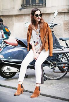 Suede fringe jacket coordinating in color with ankle booties worn with white skinny jeans.