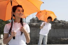 Young Chinese man and woman holding umbrellas