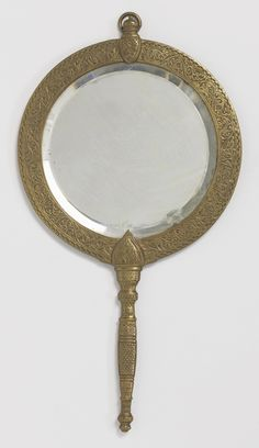 Hand mirror retailed by Tiffany and Co., New York ca. 1890.- Cast brass, cut mirrored plate. This mirror, with its trailing vine decoration, much like that seen in some of the Indian wood and metal work that Lockwood de Forest commissioned and collected in India, may well have been one of the objects that de Forest supplied to Tiffany & Company.