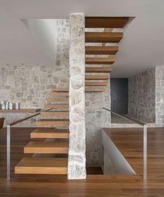 murs en pierre naturelle et escalier suspendu en bois