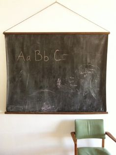"Hanging chalkboard made using ""chalk cloth"".  Other option might be to paint a roller shade with chalkboard paint, then it could re-tract like the old fashioned maps."