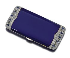 GOLD, ENAMEL AND DIAMOND CIGARETTE CASE, VAN CLEEF & ARPELS, 1920S    The rectangular curved case decorated with royal blue enamel, each side pierced and millegrain-set with calibré-cut synthetic sapphires and highlighted with rose diamonds, opening to reveal a compartment and vesta case, measuring approximately 93mm x 47mm x 8mm, signed Van Cleef & Arpels, Parisand numbered, French assay and indistinct maker's