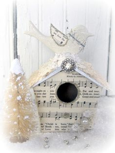 This is a charming little vintage inspired bird house! It is papier mache, painted white, and then decoupaged on the front with vintage hymnal music.