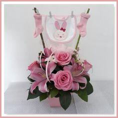 Arreglo floral con flores variadas en tonos rosado + accesorio de nacimiento niña.
