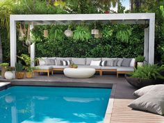 In this tropical pool area, surrounded by lush greenery, a trellis made of Ipe distressed wood in a whitewash finish frames an outdoor sectional cushioned in a gray fabric and framed in teak wood.
