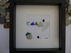 A beautiful and unique handmade pebble art picture of two birds standing on washing line with sea glass clothes blowing in the wind. This picture would make a perfect Birthday, Anniversary, Christmas etc gift. The picture has been made using pebbles, sea glass and clay. All materials have been carefully placed and fixed with high strength glue onto high quality white linen card. The black box frame is approximately 25cm x 25 cm and very good quality, and the picture has been mounted behind…
