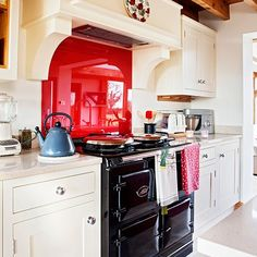 Classic cream country kitchen with Aga and red splashback