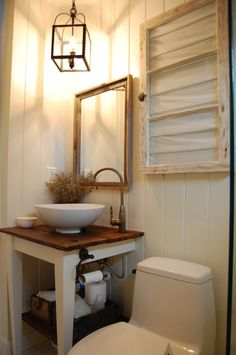 Light colours and a feature light create a sense of space in this small powder room.
