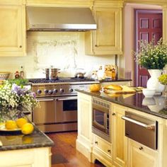 Buttery yellow cabinets and stainless steel appliances are so fresh in a kitchen. Love the pop of color on the door.