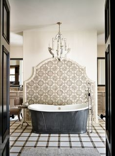Filtered Portfolio | Wiseman and Gale Interior Design, lovely tile behind tub, nice molding around tile, pretty lighting, fantastic tub, interesting floor choice, inviting dark doors coordinate with dark tub.