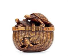 A Wood Netsuke, signed Tadakazu, Edo Period (18th-19th century) of turtles in a bamboo basket.