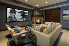Susan Brunstrum created the perfect environment for this cozy media room in her Park City, Utah vacation home design. She selected a pretty shade of blue for the walls that integrate well for television viewing. The cream-colored furniture and carpeting give the room a simple but stylish aesthetic, and the stone fireplace in the corner of the room further complements the space.