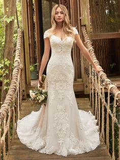 25177 - Daphne - A classically romantic lace fit-and-flare wedding dress, for getting all dressed up for that very important place to be. Gown features: Lace motifs over tulle, Sequined lace motif bodice, Captivating illusion low back, Deep illusion V-neckline, Illusion lace cap-sleeves.  Try this beauty on at Aurora Bridal in Melbourne, FL 321-254-3880