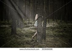 Beautiful woman hiding behind a tree in the forest. - stock photo