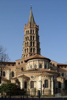 ROMANESQUE ARCHITECTURE, France - Chevet of St-Sernin, 1180, Toulouse. It was built of brick. Its multi-apsed ambulatory is strikingly articulated on the exterior. The octagonal tower was built mainly during the Gothic era.