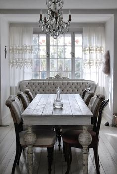 This gorgeous farmhouse dining room has both shabby chic & glamorous touches! Love the vintage table & fabulous crystal chandelier!