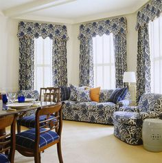 Indigo-and-white linen dominates the dining room's seating area on two club chairs, an ottoman and sofa, and in stately draperies richly gathered into side panels and topped by a scalloped valance.