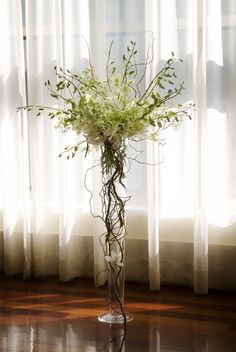 """Some of the tables will have tall centerpieces of overflowing """"lemon lime"""" hydrangeas, orange mokara orchids, """"dreaming maid"""" tulips, purple calla lilies, green lemon leaves and green hanging amaranthus on top of a 32"""