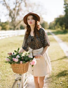 I love everything about this! the clothes, the tones, and the vintage bicycle with the basket filled with pink flowers